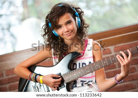 Portrait of cute teenager girl at guitar practice at home.