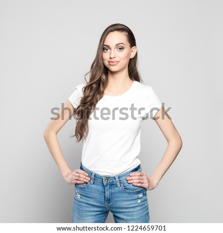 Portrait of cute teenager girl wearing white t-shirt and jeans, looking at camera. Standing with hands on hips against grey background.