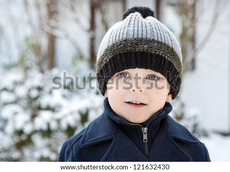 Portrait of cute toddler boy smiling on beautiful winter snowy day