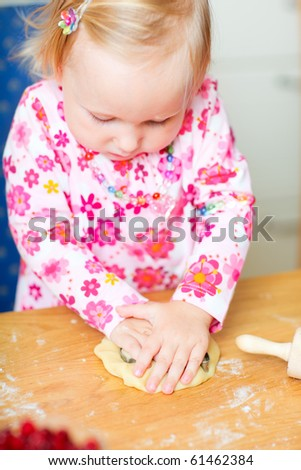 Portrait of cute toddler girl helping at kitchen with baking pie