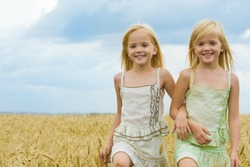 Portrait of cute twins walking down wheat field and smiling