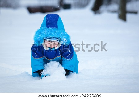 Portrait of cute 3 years old boy playing with snow outdoors