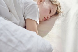 Portrait of cute young boy sweetly sleeping in bed