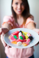 Portrait of Cute young woman eating jelly candies with a fresh smile