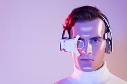 Portrait of cyborg in headphones and digital eye lens on purple background