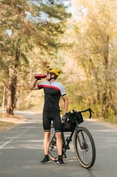 Portrait of cyclist in sportswear standing with bicycle on road in autumn forest and drinking water from bottle. Thirsty cyclist athlete rests on training, drinks water. Vertical