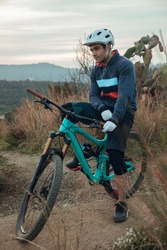 Portrait of cyclist rider with blue enduro bike on mountain bike trail in Barcelona mountain. Ready to go down the track