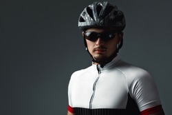 portrait of cyclist wearing helmet on gray background. copy space