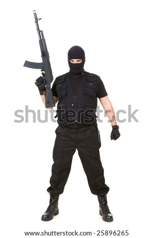 Portrait of dangerous bandit in black wearing balaclava and holding gun in hand