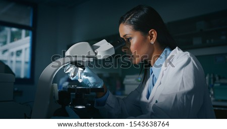 Portrait of dark skin female scientist is analyzing a sample to extract the DNA and molecules with microscope in laboratory.