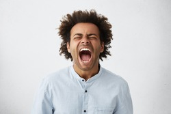 Portrait of dark-skinned African guy with curly hair screaming with wide opened mouth closing his eyes in despair having unhappy expression. Frustrated male shouting loudly having aggression