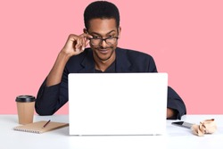 Portrait of dark skinned man works with laptop. Handsome black male sits at desk wears suit, touches his spectacles with hand, looks concentrated at monitor. Online working and technology concept
