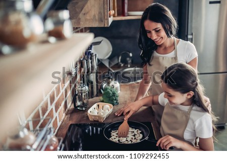 portrait of daughter and mother frying mushrooms on the stove together for dinner at the kitchen