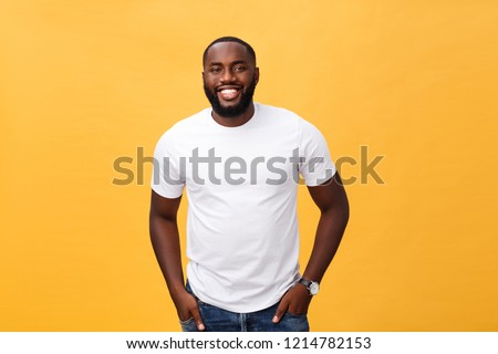 Portrait of delighted African American male with positive smile, white perfect teeth, looks happily at camera, being successful enterpreneur, wears white t shirt. #1214782153