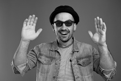 Portrait of delighted attractive man in casual stylish clothes keeping his hands up while smiling broadly