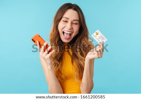 Portrait of delighted joyous caucasian woman holding cellphone and credit card isolated over blue background in studio