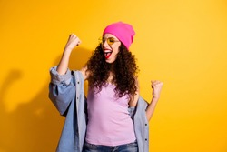 Portrait of delighted positive girl raise fists scream yeah celebrate victory in competition wear denim jeans jacket pink tank-top isolated over yellow color background