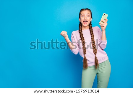 Portrait of delighted sweet youngster girl blogger use smartphone get social network like notification raise fists scream omg wow wear pullover green pants trousers isolated shine color background