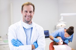 Portrait of dentist standing with arms crossed in clinic