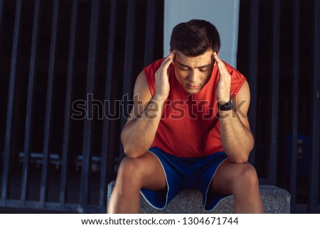Portrait of depressed man touching head with arm while feeling pain after training