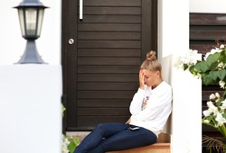 Portrait of  depressed  woman sitting on stairs at home.Crying woman