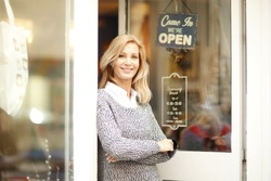 Portrait of designer woman standing in front of small vintage store. Small business.