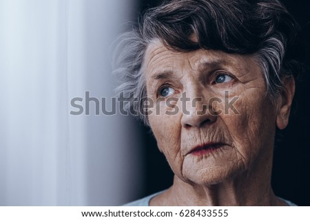 Portrait of despair, old woman standing beside window