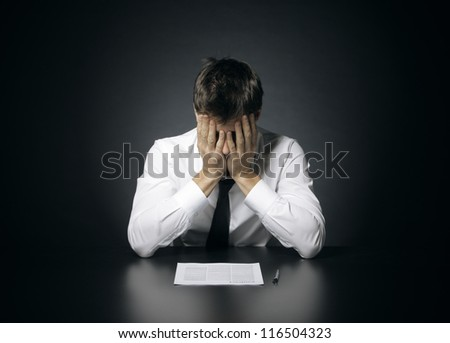 portrait of desperate office manager  covering his face with both hands