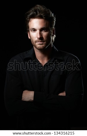 Portrait of determined goodlooking man wearing black shirt, black background.