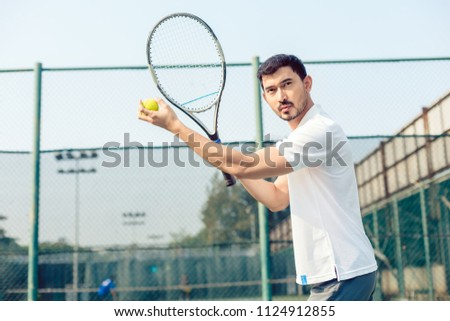 Portrait of determined tennis player looking forward with concentration before serving during a challenging match #1124912855