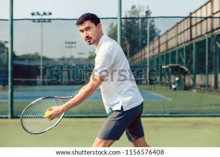 Portrait of determined tennis player looking forward with concentration before serving during a challenging match #1156576408