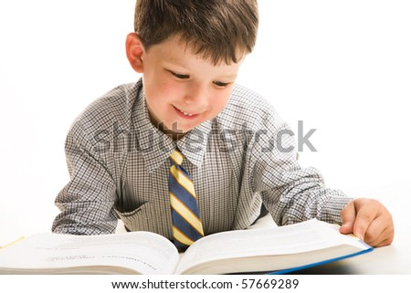 Portrait of diligent schoolboy in casual clothing reading the book