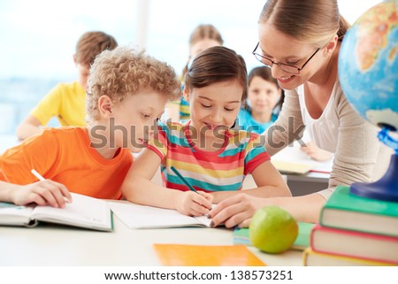 Portrait of diligent schoolgirl drawing at lesson surrounded by her classmate and teacher - stock photo