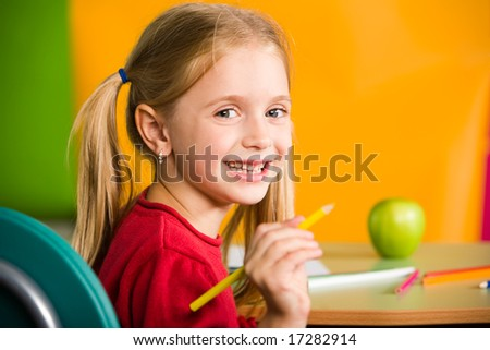 Portrait of diligent schoolgirl with pencil looking at camera during lesson