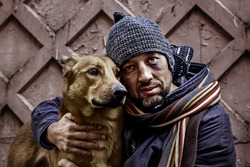 Portrait of dirty tramp hugging his dog. Image with toning and selective focus