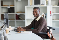 Portrait of disabled African-American man using computer and smiling at camera while studying in college library, copy space