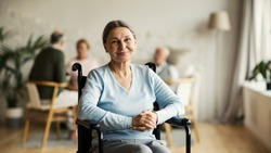 Portrait of disabled senior woman in wheelchair looking at camera and smiling happily in nursing home; other aged patients in background
