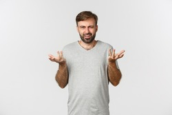 Portrait of disappointed and confused man with beard, raising hands up and complaining, standing in gray t-shirt over white background