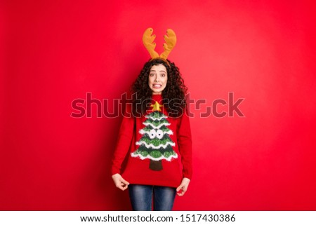 Portrait of disappointed funny funky crazy girl in reindeer horned headband student show her granny newyear present ugly stylish sweater with christmas tree ornament isolated red color background