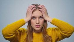 Portrait of disappointed woman feeling doubtful on grey background. Closeup pensive lady posing with shocked face in studio. Upset attractive girl looking at camera.