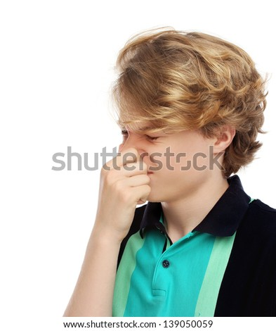 Portrait of disgusted teenage boy pinches her nose. White background - stock photo