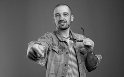 Portrait of displeased man in denim jacket expressing disrespect while pointing at you and holding his spectacles in hand