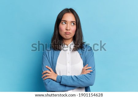 Portrait of displeased offended young Asian woman with dark hair keeps arms folded looks angrily aside doesnt agree with somebodys opinion wears neat clothes isolated over blue studio background Сток-фото ©
