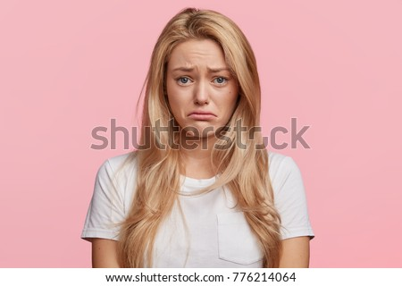 Portrait of displeased upset female frowns face as going to cry, being discontent and unhappy as can`t achieve goals, isolated over pink studio background. Dissapointed young woman has troubles