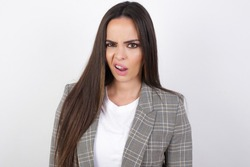 Portrait of dissatisfied young beautiful caucasian businesswoman standing against white wall smirks face, purses lips and looks with annoyance at camera, discontent hearing something unpleasant
