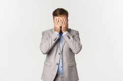 Portrait of distressed and exhausted businessman in grey suit, hiding his face behind hands, standing over white background