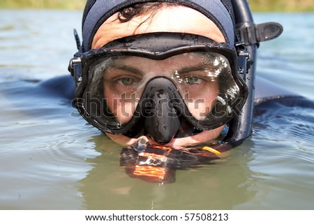 portrait of  diver in  diving suit and  mask looking out of the water. Close-up
