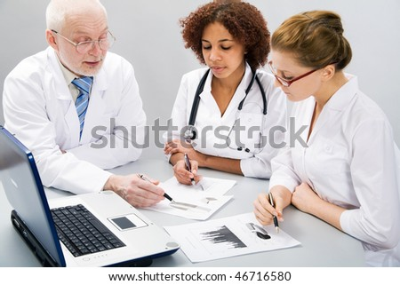 Portrait of doctor explaining computer work to coworkers