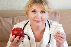 Portrait of doctor giving apple and pills in blister, medicine therapeutist doctor hands holding red fresh ripe apple and medicines, closeup
