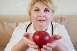 Portrait of doctor giving apple, medicine therapeutist doctor hands holding red fresh ripe apple, closeup